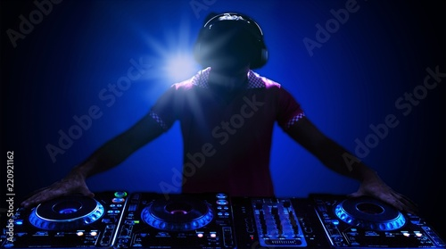 Portrait of confident young DJ with headphones on head mixing - 220921162