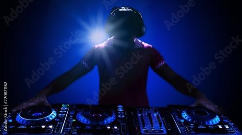 Leinwanddruck Bild Portrait of confident young DJ with headphones on head mixing