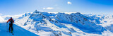 Ski in winter season, mountains and ski touring man on the top in sunny day in France, Alps above the clouds.