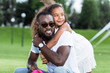 adorable african american daughter hugging father from back in park