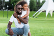african american daughter hugging father from back in park and they looking away
