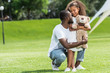 african american father squatting and hugging adorable daughter with teddy bear in park