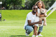 african american father and daughter with teddy bear looking at camera in park