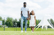 african american policeman with gun and daughter holding hands and walking at amusement park