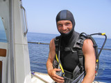 smiling diver on a boat in the Mediterranean sea preparing for a dive - 220931761