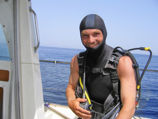smiling diver on a boat in the Mediterranean sea preparing for a dive