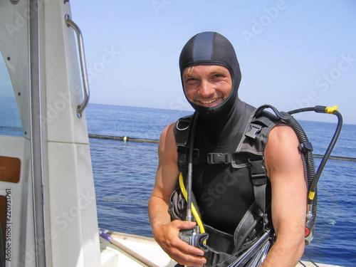 uśmiechnięty nurek na łodzi na Morzu Śródziemnym, przygotowując się do nurkowania