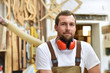 portrait of a carpenter in work clothes and hearing protection in the workshop of a carpenter's shop