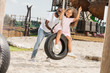 african american father pushing daughter on tire swing at amusement park