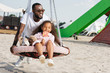 african american father pushing daughter on spider web nest swing with lollipop at amusement park