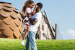 african american father holding happy daughter on green hill at amusement park