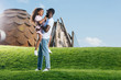 african american father holding smiling daughter on green hill at amusement park