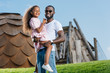 smiling african american father holding daughter on green hill at amusement park