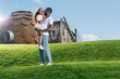 cheerful african american father holding daughter on green hill at amusement park