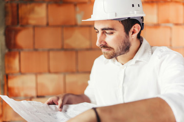 Young engineer on construction site on brick wall