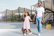 smiling african american father and daughter holding hands and walking at amusement park