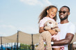 smiling african american father holding daughter and they looking at camera