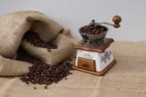 Alte Kaffeemühle mit eingefüllten Kaffeebohnen neben einem Kaffeesack - 220933743