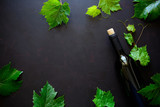 Bottle of red wine, grapes and leaves lying on dark wooden background. Top view. Flat lay. Copy space - 220935385