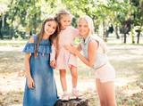 Little girls stand hugging in a sunshine autumn park - 220936993