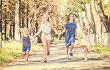 Little smiling girls running on the sunshine autumn alley by holding hands - 220937193