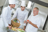 chief chef watching his assistants garnishing a dish - 220943967