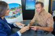 Man at travel agents making card payment