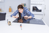 Woman fitting ceramic hob into kitchen unit - 220950904