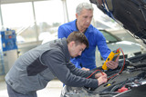 auto mechanic teacher and trainee performing tests at mechanic school - 220958573