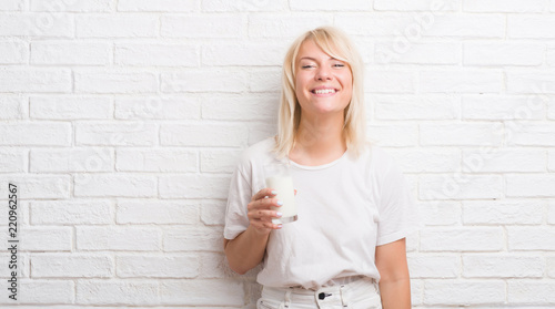 Leinwandbild Motiv Adult caucasian woman over white brick wall drinking glass of milk with a happy face standing and smiling with a confident smile showing teeth