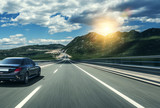 Black car rushing along a high-speed highway in the sun. - 220963316