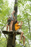 friends climbing rope at the adventure park - 220963975