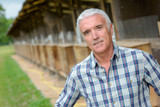 Portrait of man in front of barn - 220965794