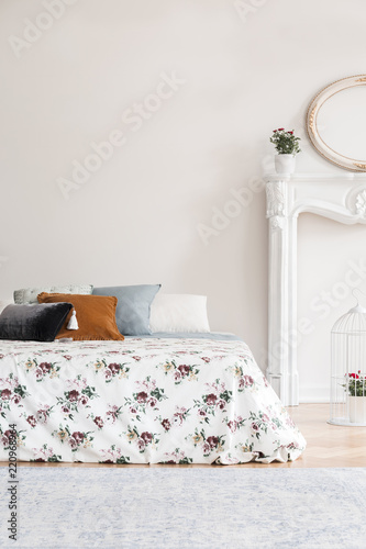 Leinwanddruck Bild Feminine English style bedroom interior with a bed with rose pattern cover and multicolor pillows against an empty copy space wall. Real photo.