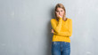 Leinwanddruck Bild - Beautiful young woman standing over grunge grey wall thinking looking tired and bored with depression problems with crossed arms.