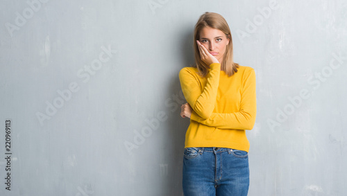 Leinwanddruck Bild Beautiful young woman standing over grunge grey wall thinking looking tired and bored with depression problems with crossed arms.