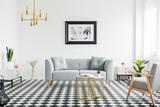 Poster above grey sofa in bright patterned living room interior with armchair and gold lamp. Real photo - 220969360