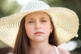 portrait of a little girl wearing a big hat, beautiful sunny day, bright sun and shadows, face closeup - 220976903