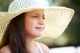 portrait of a little girl wearing a big hat, beautiful sunny day, bright sun and shadows, face closeup - 220976958