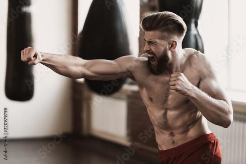 Leinwanddruck Bild Athletic Male Boxer Training at Boxing studio
