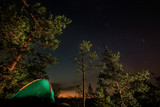 Night scene with illuminated camping tent, forest and starry sky - 220985181