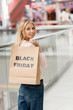 smiling young woman holding paper bag with lettering black friday and looking at camera at shopping mall