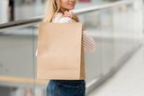 partial view of young woman holding paper bag at shopping mall - 220985302