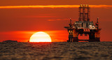 drilling platform on the ocean during sunrise - 220987166