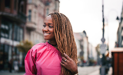 Beautiful smiling African girl walking in the city street