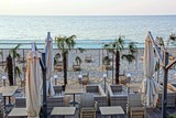 sunbeds and furniture with umbrellas on the beach with palm trees in the sand against the sky and the sea - 220990719