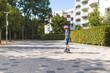 Ein 9 Jahre altes Mädchen skatet auf einem Skateboard auf einem Platz vor einem Wohnblock
