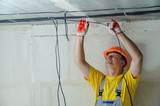 An electrician is fixing an electric cable. - 220997374