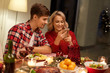 holidays, technology and celebration concept - happy couple having christmas dinner at home and using smartphone