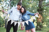 young couple posing with flags in the forest, summer nature, romantic feelings - 221008916
